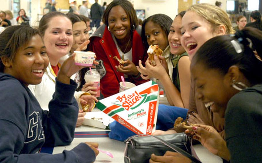 Lakenheath High School sophomores, left to right, Andrea Gafford, Jennifer Bracken, Brittney Blue, Keierra Isaac, Tanishia Joynek, Holland Lewis, Joy Heiserman and Desha Williams laugh over lunch recently at the Lakenheath BX food court. With little money and a loathing for the school cafeteria, the girls said they come to the food court for a hot dog, slice of pizza, some chicken wings or a cup of ice cream for lunch.