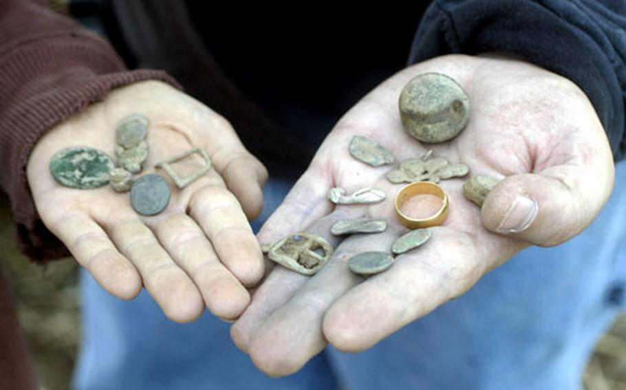 Steve and Jon Reese hold up their finds during a recent day of metal detecting near Birmingham, England. Besides various coins, Steve found a 22 karat gold ring and an old bell, a belt buckle and a small, detailed piece of silver.