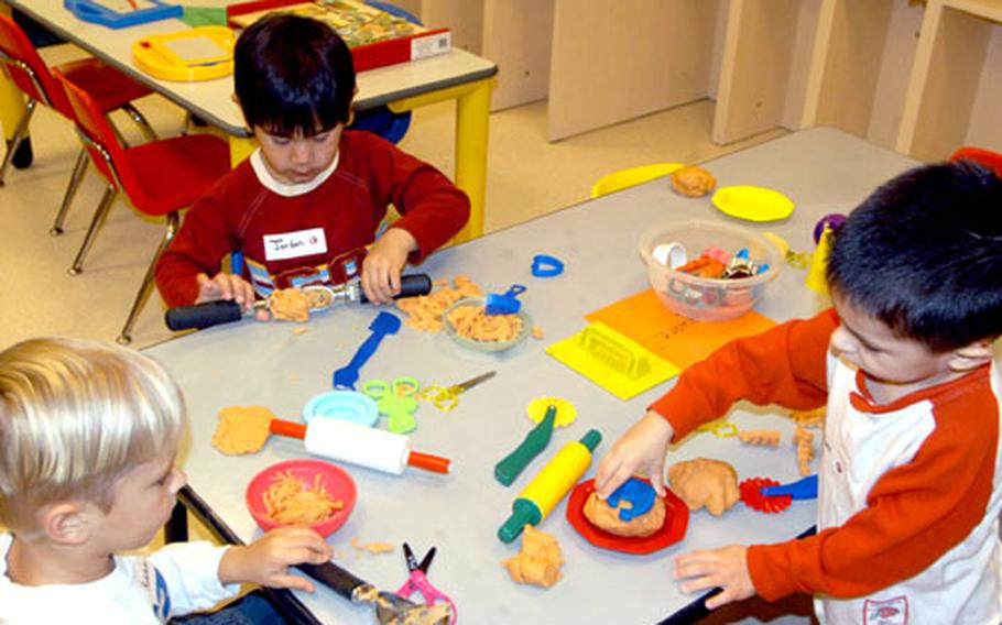 Clockwise from left: Robbie Stiles, Jordan Nives and Alex Lopez work with Play-Doh during a half-day enrichment period at the new Child Development Center at Aviano, Italy.