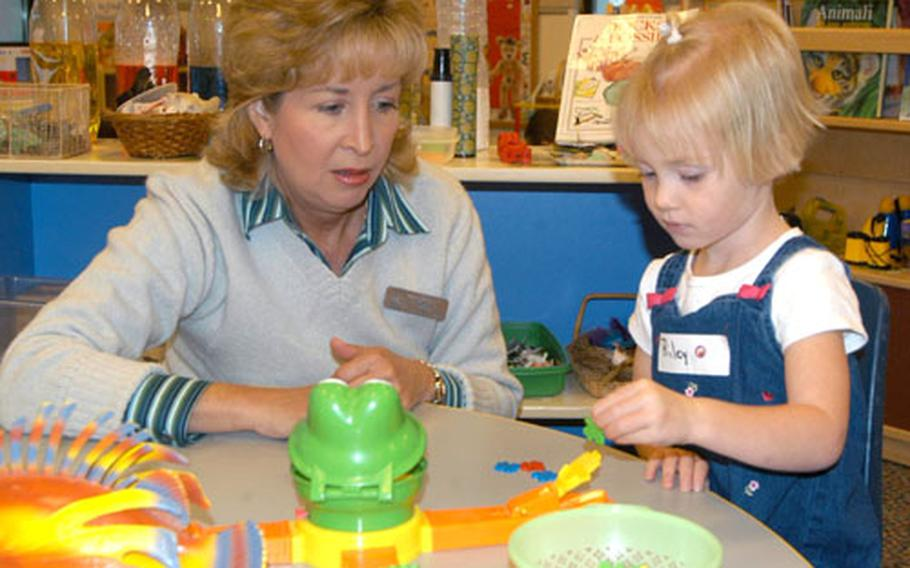 Jan Mead, one of the instructors of the part-day enrichment program at the new Child Development Center at Aviano, shows Riley Williams a new toy at the center on Tuesday.