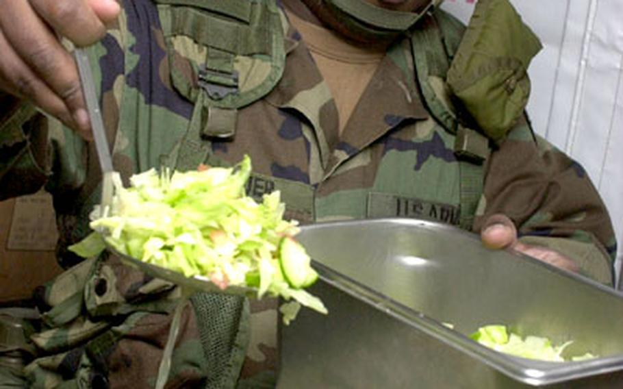 Army Spc. Narlin Ramsuer, a soldier with the 29th Headquarters, Headquarters Company at Rhine Ordnance Barracks in Kaiserslautern, Germany, dishes a scoop of salad into a serving container on Tuesday.