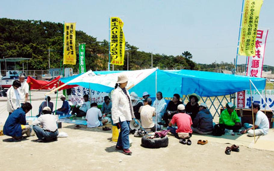 Okinawans line Highway 330 near Camp Schwab on Jan. 18, part of an ongoing protest by anti-base activists and environmentalists against an air station proposed at the island's Henoko port. U.S. and Japanese officials announced Wednesday that the facility would not be built at Henoko.