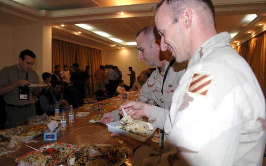 Local Iraqi leaders and U.S. Army officials dig into a feast celebrating the end of the day's Ramadan fast. The occasion was further sweetened by the announcement of the passage of the Iraqi constitutional referendum.