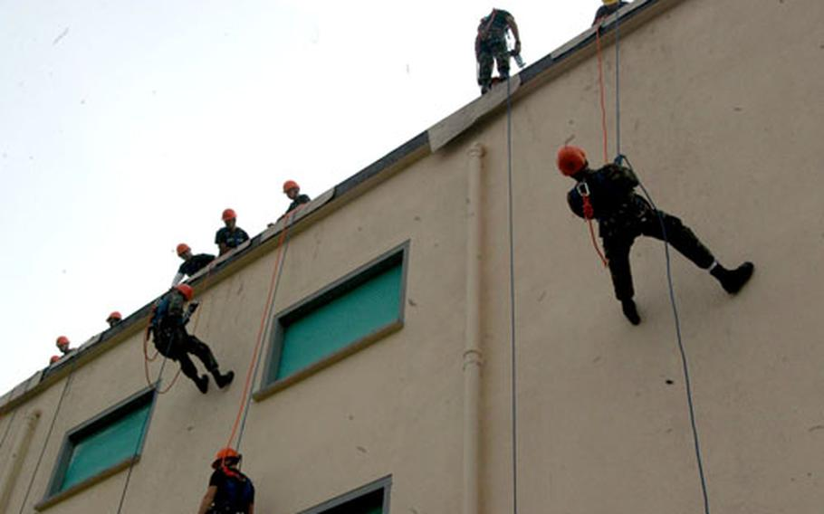Aviano Air Base firefighters rappel down a building on base Wednesday.