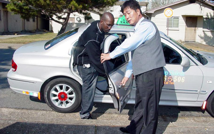 A taxi driver holds the door for a passenger at Camp Hialeah in Busan, South Korea, in November, 2003. Hialeah officials scrapped the service in July after patrons found it tough to find a cab.