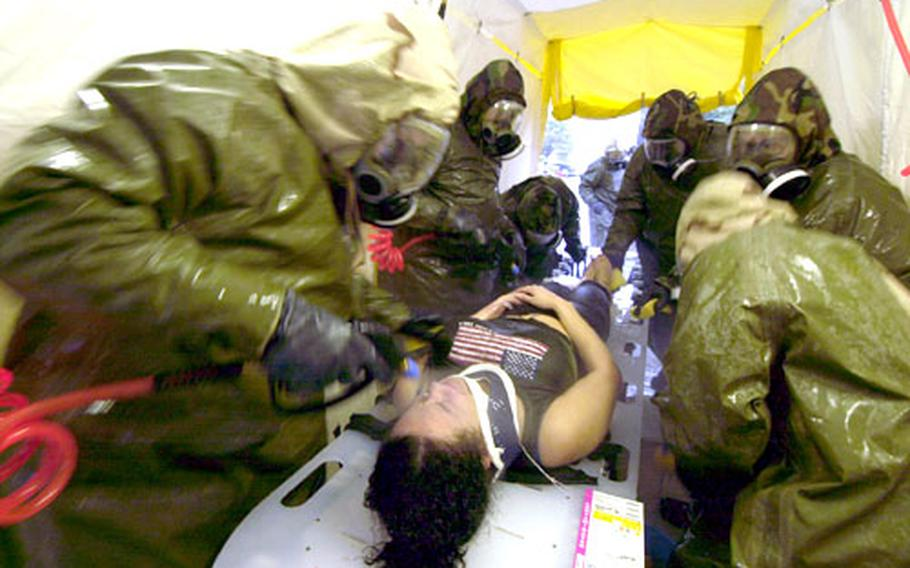 """Hospital corpsmen attached to U.S. Naval Hospital Yokosuka wash """"victims"""" inside a chemical wash station during a joint medical training with Japanese forces at the base on Wednesday."""