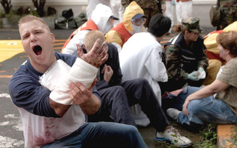 """Corpsman Samuel Karr yells for help Wednesday after """"suffering"""" 2nd- and 3rd-degree burns during a simulated terrorist attack at Yokosuka Naval Base. None of the injuries were real, but the victims were convincing."""