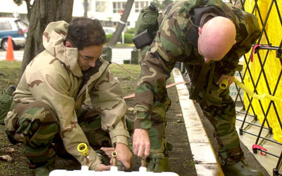 Petty Officer 1st Class Rubi Cedeno and Lt. Cmdr. Alan Ross set up the water supply for a chemical wash station during the exercise at Yokosuka.