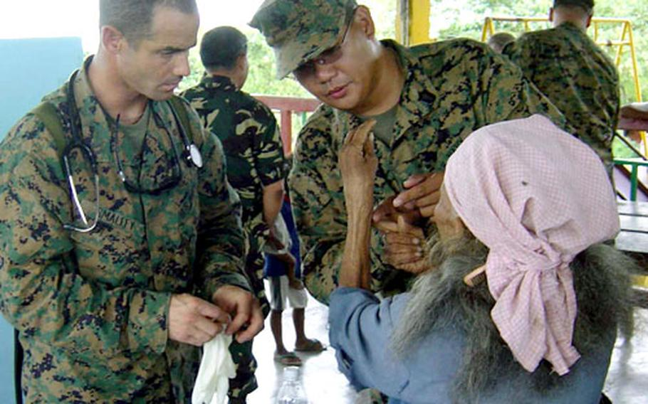 Navy Lt. Val Smalley, left, a physician assigned to Marine Service Support Group 31, and Petty Officer 1st Class Joel Clemente, a corpsman attached to the 3rd Marine Expeditionary Force Special Operations Training Group, examine the wrist of an elderly woman who traveled from a nearby village seeking medical care. U.S. Navy, Marine Corps and Armed Forces of the Philippines medical personnel provided health care to about 900 residents of Gawad Kalinga Village, Barangay Santa Juliana, Capas and Tarlac.