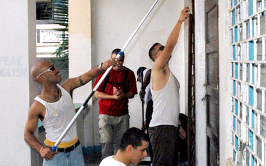 USS Essex sailors paint the two-story Gordon Heights Elementary School in Olongapo City, Philippines, as part of the ship's community relations project.