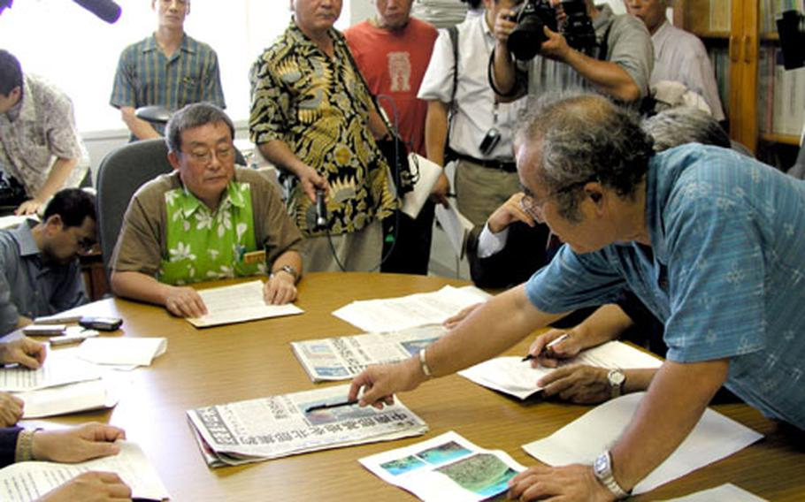 Reiji Fumoto, councilor for the Okinawa prefectural government's military affairs office, seated at center, meets Thursday with about 20 anti-military advocates in Naha. Hiroshi Ashitomi, standing, demanded Gov. Keiichi Inamine reject a new plan to move Marine Corps air station operations to the Camp Schwab area.