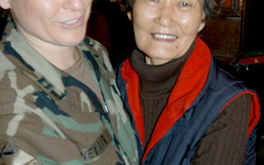 Camp Kyle's last commander, Capt. Bridget Wetzler, gets a goodbye hug from Edee Wa club bartender Kim Yong-Hui on Wednesday.