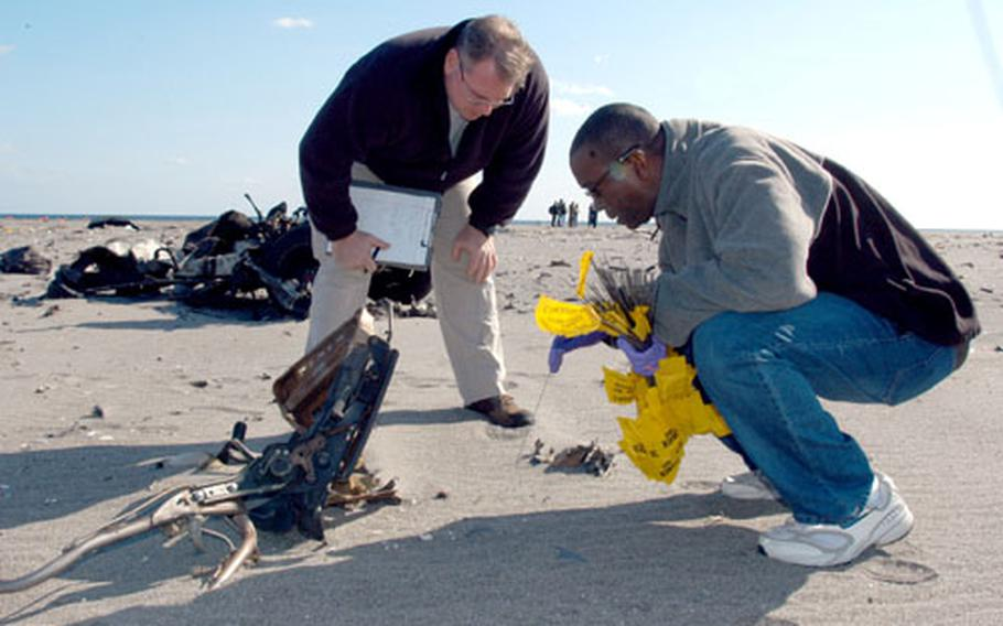 Frank Boyd, left, and Brian Curley, Naval Criminal Investigative Service agents from Singapore, examine fragments from a vehicle explosion at Draughon Range near Misawa Air Base, Japan, on Wednesday as part of FBI-led bomb scene analysis training for military and civilian criminal investigators and bomb specialists.