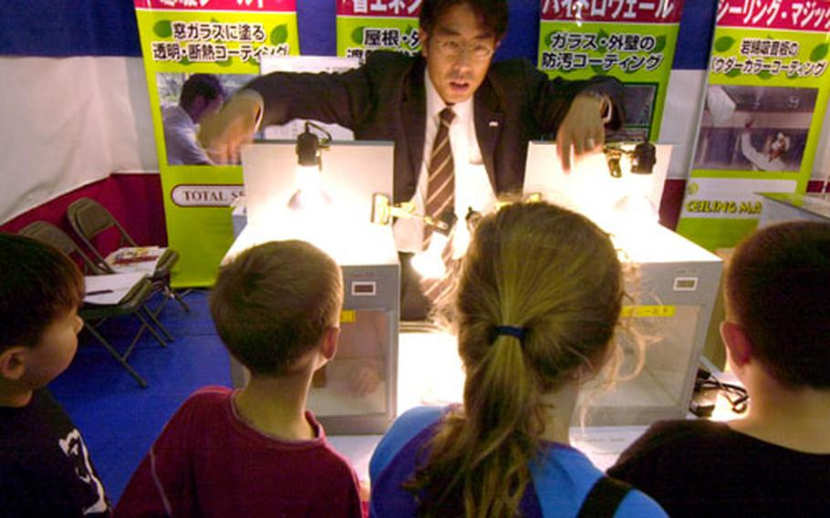Christa Ortman's third grade class listens to Tomonoti Shibazaki explain how light effects different surfaces during the energy fair at Naval Air Facility Atsugi on Thursday.