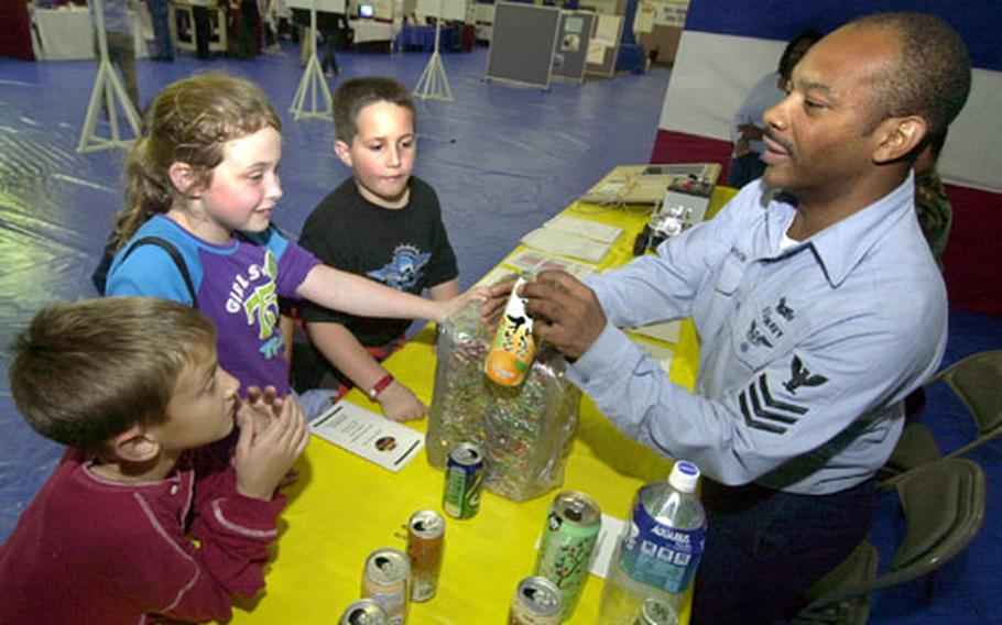 Petty Officer 1st Class Michael Robinson shows third graders how many cans fit into this crushed cube of metal as part of his exhibit at the energy fair at Naval Air Facility Atsugi on Thursday.