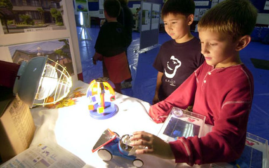 Noah Johnson and Eric Johnson of Christa Ortman's third grade class check out a solar panel exhibit on display during the energy fair at Naval Air Facility Atsugi.
