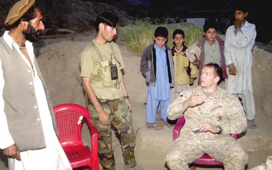 Marine 1st Lt. Matt Bartels, commander of Camp Blessing, right, talks with an Afghan Security Forces troop and a villager Thursday evening outside the camp in eastern Afghanistan's Kunar province. Solid relationships with local Afghans have led to the seizure of thousands of pounds of enemy ordnance since the Marines arrived at Blessing in June.