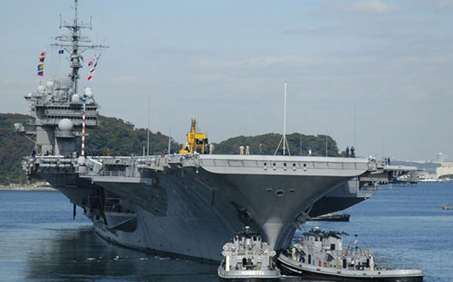 Assisted by two harbor tug boats, the USS Kitty Hawk steams away from the pier at Yokosuka Naval Base, Japan, to begin its fall underway period. Navy officials announced Friday the Kitty Hawk will be replaced in 2008.