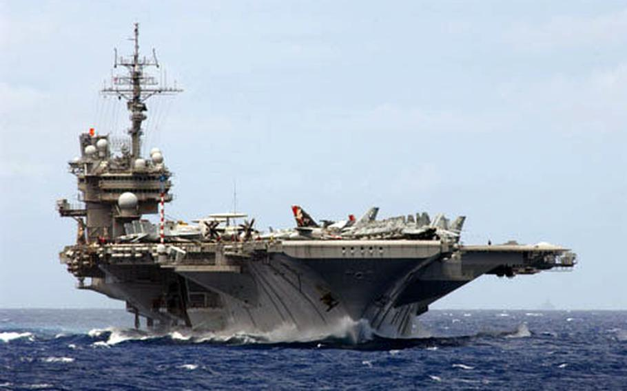USS Kitty Hawk plows through the waters of the Pacific Ocean in 2004.