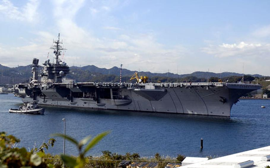The USS Kitty Hawk steams away from the pier at Yokosuka Naval Base, Japan, to begin its fall underway period.