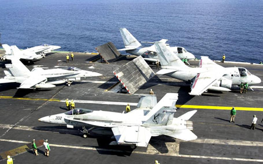 U.S. Navy combat aircraft line up on the flight deck of the USS Kitty Hawk in Dec. 2001.