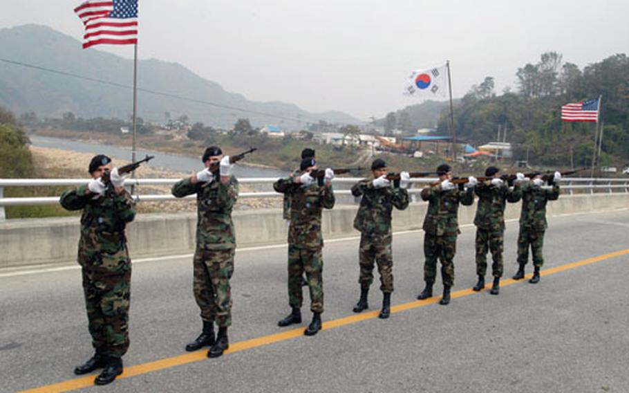 U.S. soldiers fire a salute on the during the dedication ceremony.