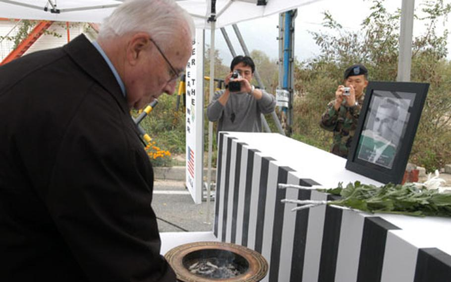 James Livingston lights incense during a ceremony dedicating a bridge in South Korea to his brother, 2nd Lt. Thomas W. Livingston Jr.
