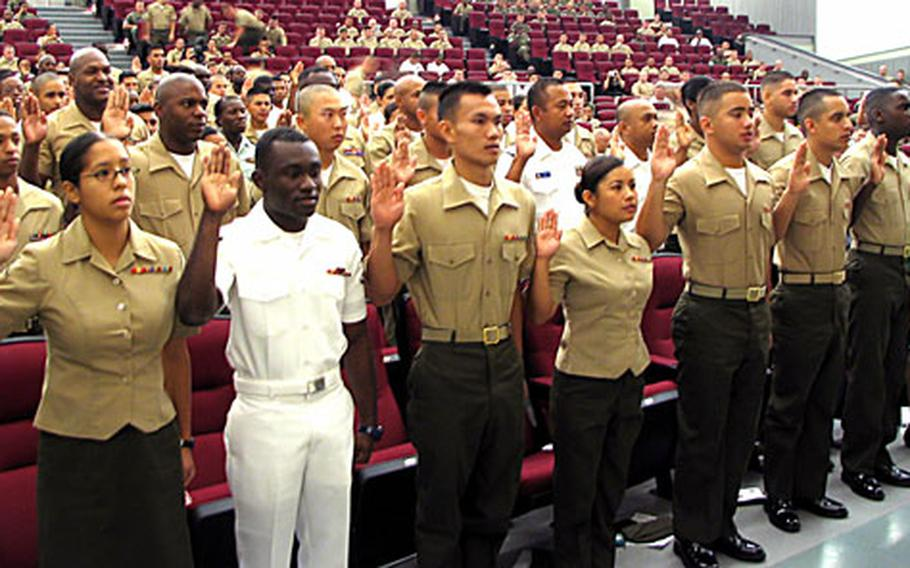 U.S. servicemembers take the oath of American citizenship Friday during a naturalization ceremony on Camp Foster, Okinawa.