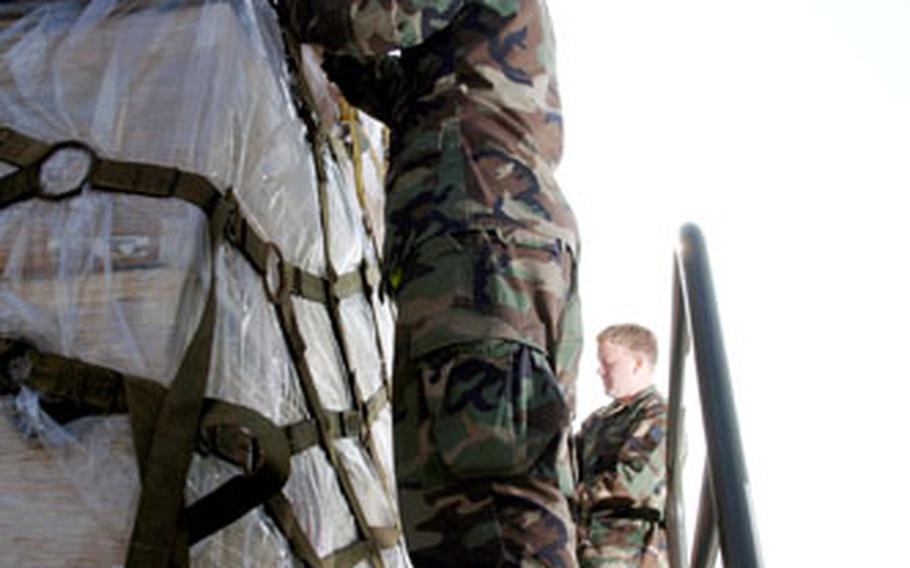 Timothy Stedelin, foreground, and Roy Biddle, senior airmen serving as air transportation specialists with Yokota Air Base's 730th Air Mobility Squadron, check the straps of cargo pallets loaded with relief supplies bound for Pakistan.