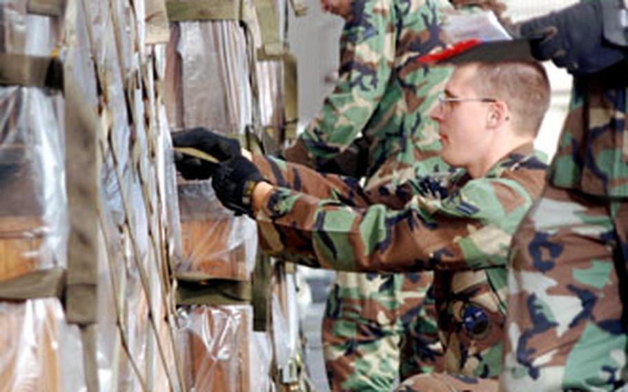 Airmen from Yokota's 730th Air Mobility Squadron tighten the straps of cargo pallets destined for earthquake relief in Pakistan. The unit loaded 71,710 pounds of relief supplies from U.S. Army Japan onto a plane that left Saturday.