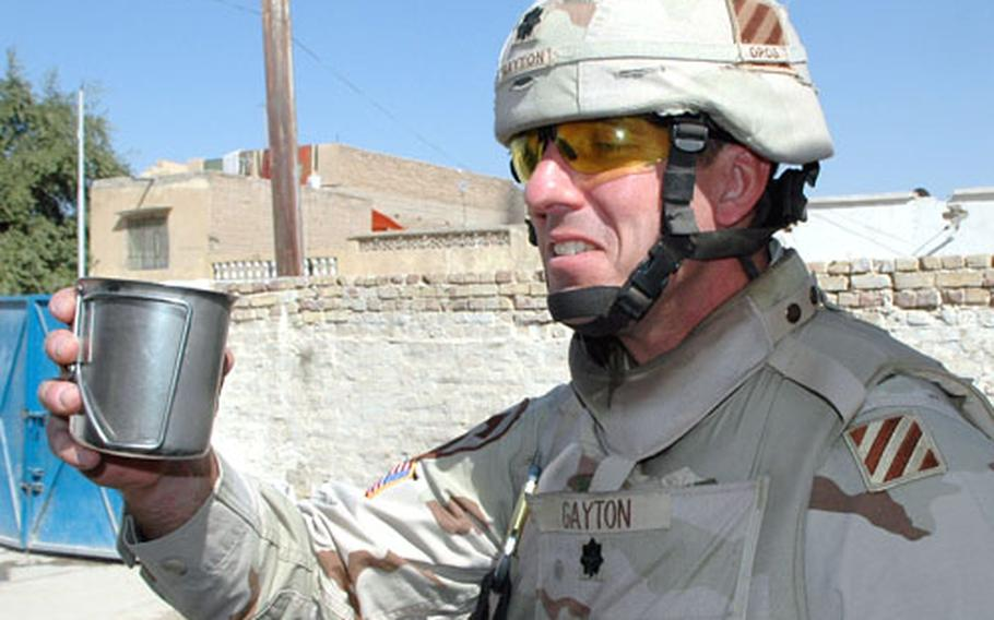 """Lt. Col. Jamie Gayton samples water from a $100,000 water purification system installed at a local school. """"It tastes good,"""" he said."""