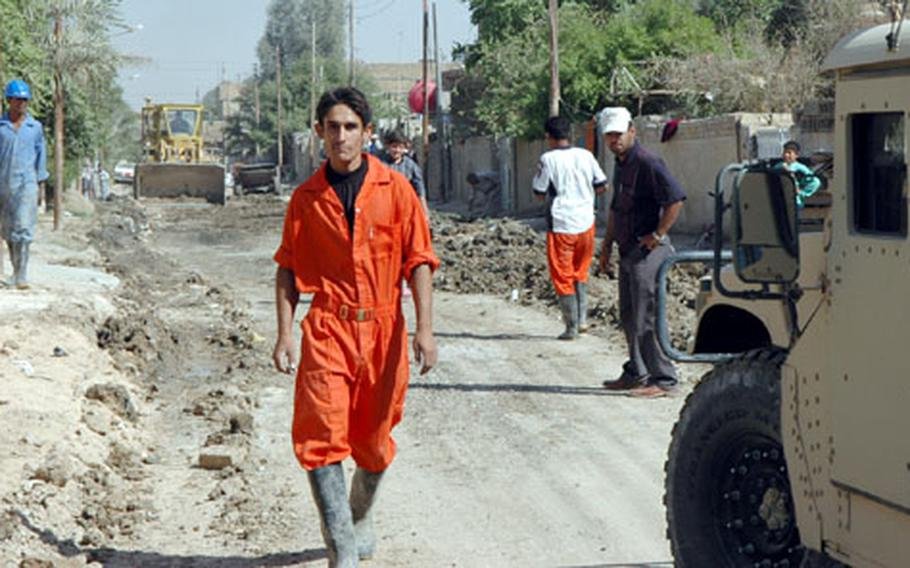 Jumpsuited workers fill the streets of Tissa Nissan, a poor neighborhood in eastern Baghdad. The workers are installing the area's first underground sewer system.