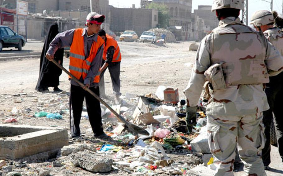 Local workers shovel trash from collection points into trucks in Sadr City.