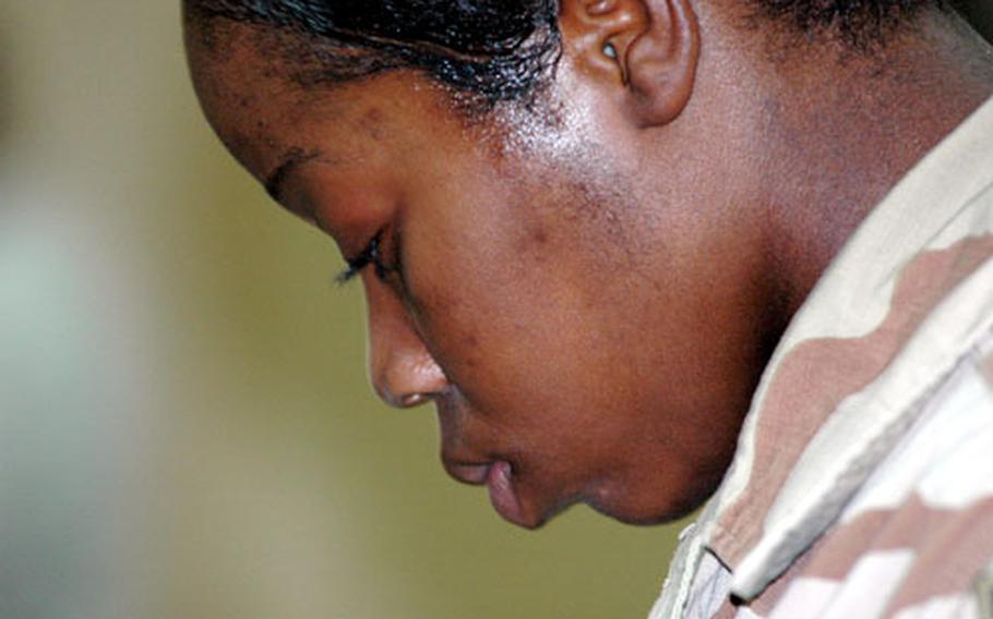 Spc. Natasha David of Brooklyn, N.Y., lowers her head in prayer at FOB Warhorse.
