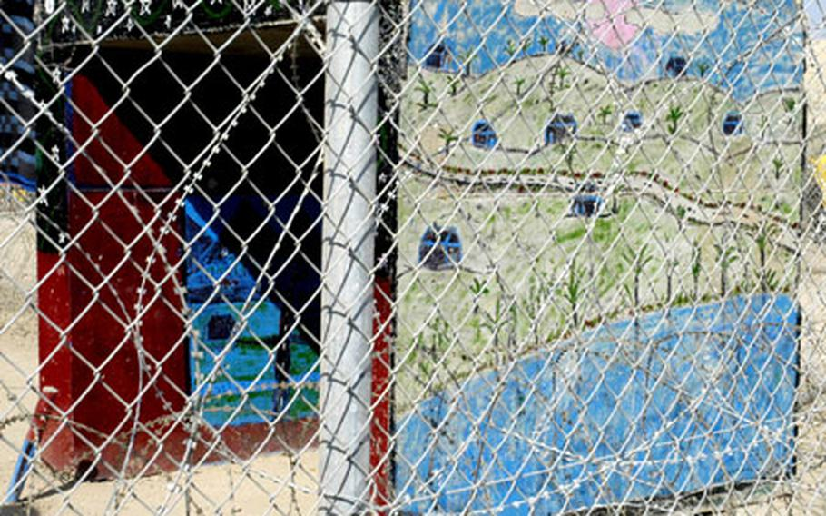 Two of the winning entrants of an art contest for young Abu Ghraib detainees, as seen through a fence.