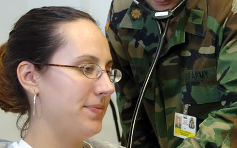 Dr. (Maj.) Mike Simpson examines Gena Hernandez at the Darmstadt Clinic on Monday.