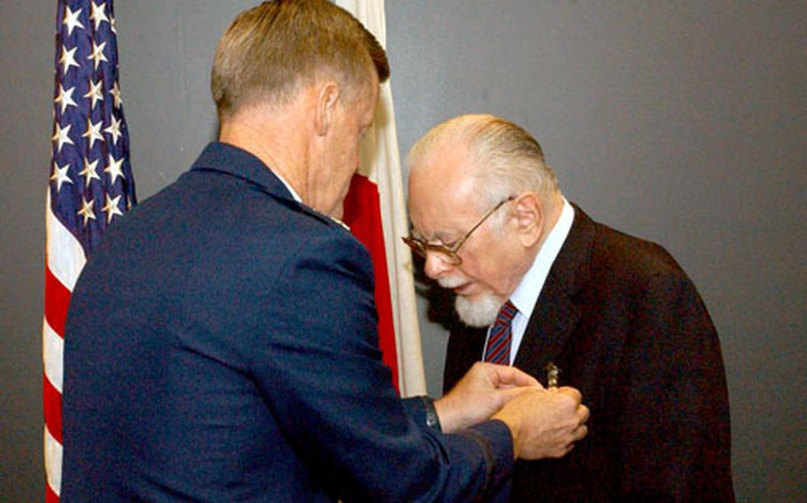 Air Force Lt. Gen. Bruce Wright, commander of U.S. Forces Japan and the 5th Air Force, pins the Silver Star on retired Maj. Jesse Foster more than 60 years after he earned it for gallantry in action during World War II.