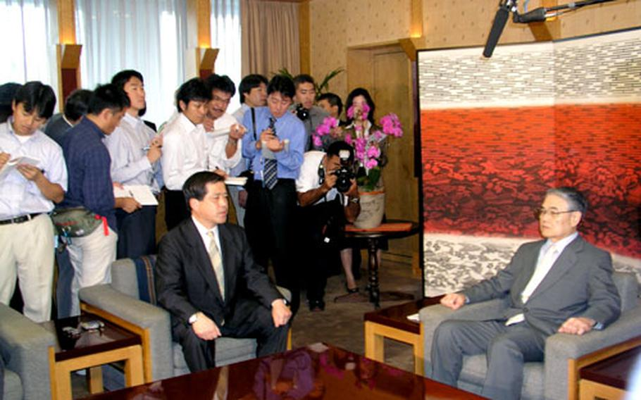 Iwao Kitahara, Director General of Japan's Defense Facilities Administration Agency, left, meets with Okinawa Gov. Keiichi Inamine Monday in Naha.