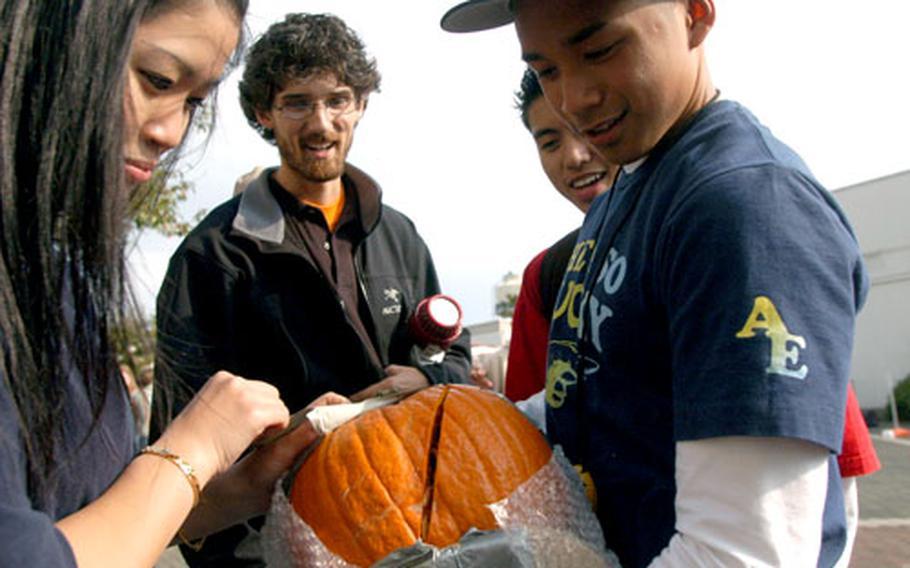 Yoko James and Jener Delos Santos show Nile C. Kinnick physics teacher Ryan Goodfellow the injuries their pumpkin sustained during a 65-foot drop Monday.