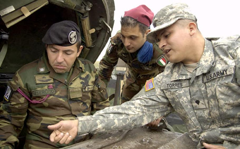 Spc. Juan Torres of 1st Squadron, 1st Cavalry Regiment, shows Italian Warrant Officer Vinoenz Blotta, in hatch, and another unnamed soldier, the controls of an M3A2 Bradley Armored Fighting Vehicle during Exercise Urgent Quest on England's Salisbury Plain.