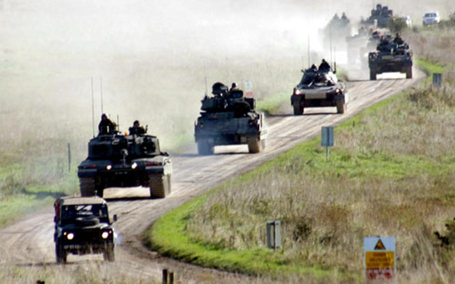 A convoy of armored and unarmored vehicles from the United Kingdom, United States, Italy, Sweden, and France moves toward a battle position during Exercise Urgent Quest.