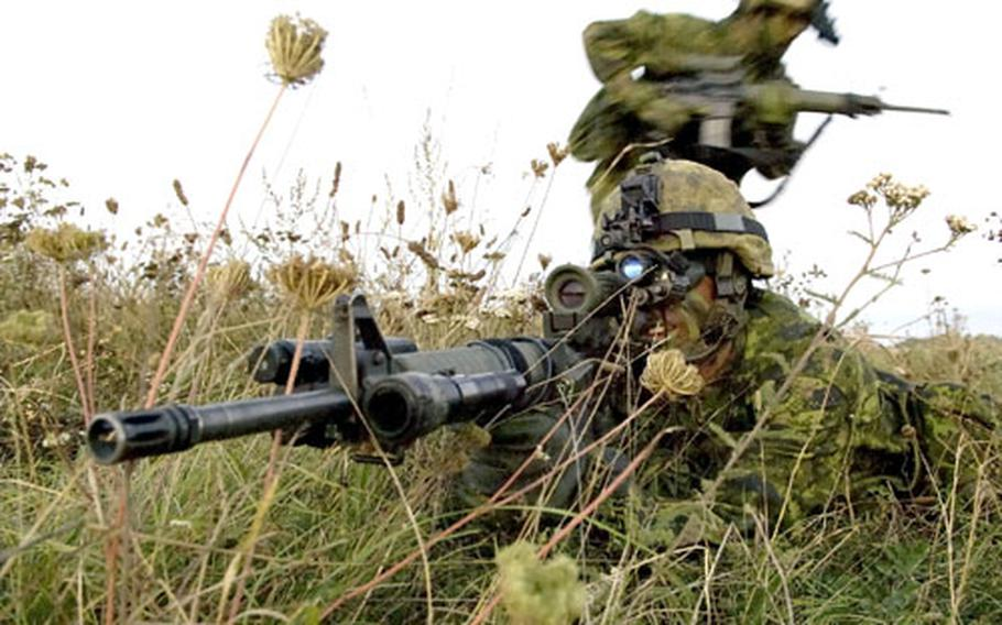 """Two Canadian soldiers assigned to the Black Watch battle group take up positions in an English field on the Salisbury Plain Training Area during Exercise Urgent Quest. The exercise was desgined to test various equipment used to minimize """"friendly fire"""" incidents."""