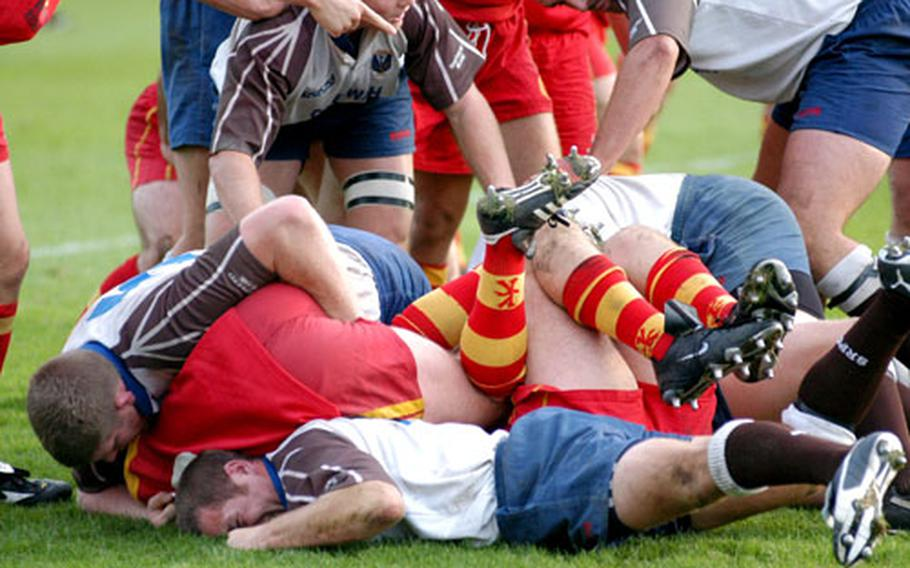 Bodies jarred and limbs akimbo, members of the Cambridge Rugby Union Football Club and the Southend Rugby Football Club pile up in a fight for the ball.