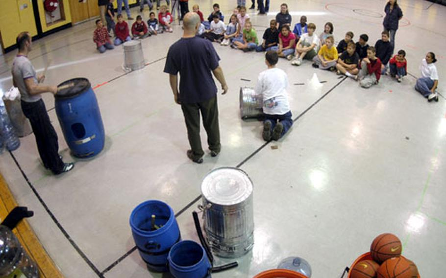 """Paul Gunter, at drum, and Dave Gallagher of the London musical """"Stomp"""" talked to elementary school students at RAF Alconbury last week about music, rhythm, and even counting."""