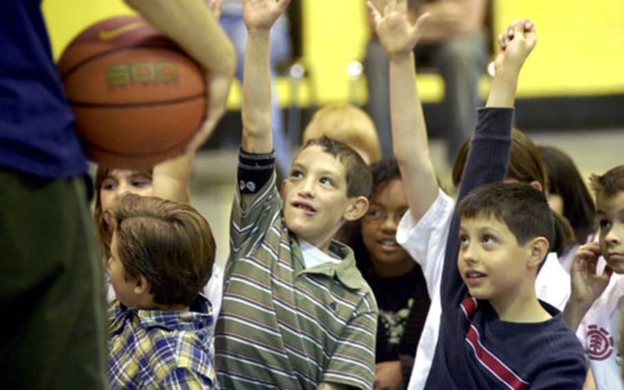Alconbury Elementary School students Anthony Walker and Thomas Tarach hold their hands up in hopes of being picked to help with a musical demonstration with a basketball.