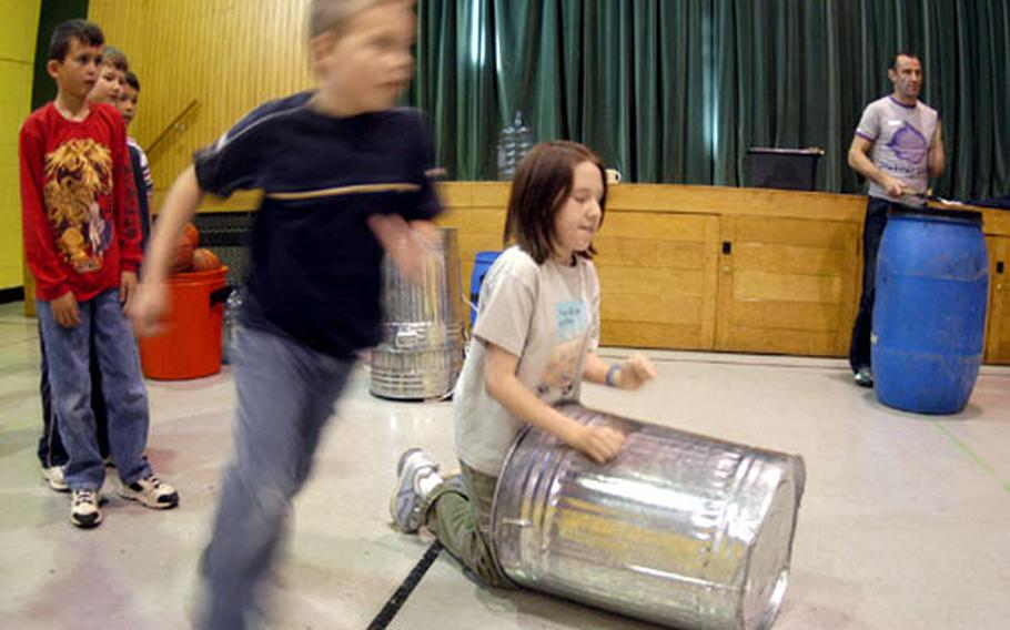Serenity McKenzie bangs on a garbage can as David Dougherty runs around her at the Alconbury Elementary School gym.