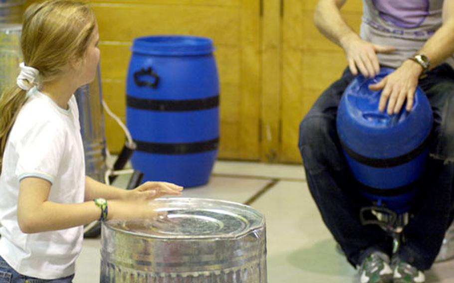 Alconbury Elementary School's Mattea Swegles beats on the back of a trash can, trying to keep beat with Stomp performer,Paul Gunter, at back.