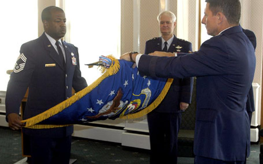 Maj. Gen. Michael Gould rolls up the 3rd Air Force flag Tuesday at RAF Mildenhall as deputy U.S. Air Forces in Europe commander Lt. Gen. Rod Bishop watches. Holding the flag as Gould rolls it is Chief Master Sgt. Derrick M. Candler.