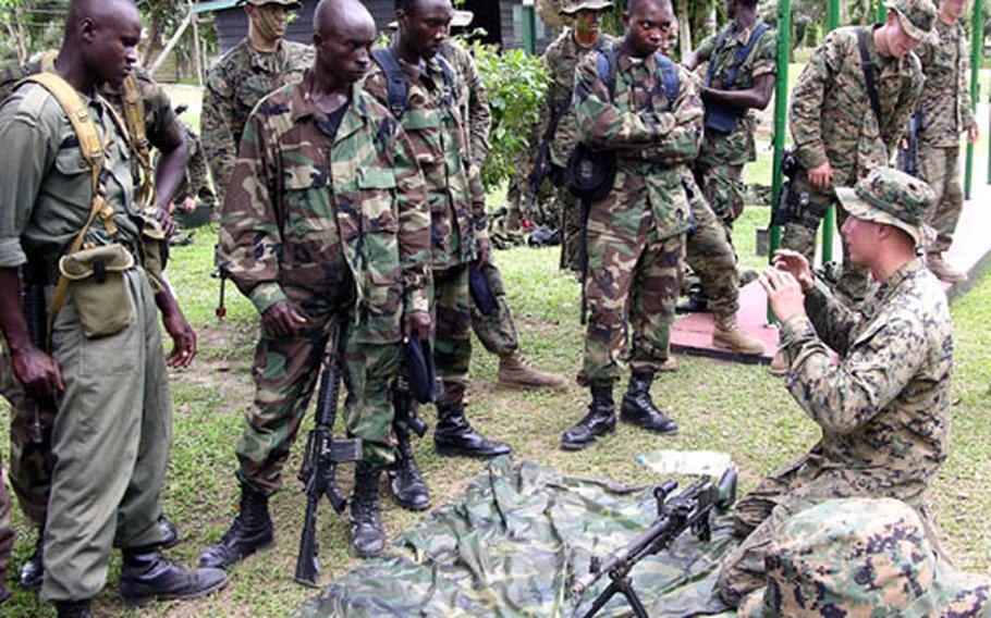 Marine Cpl. Richard Hazenburg of 2nd Platoon, Company C, 1st Battalion, 8th Marine Regiment, instructs Ghanaian soldiers on the M-240G medium machine gun at a jungle warfare school during the West African Training Cruise 06.