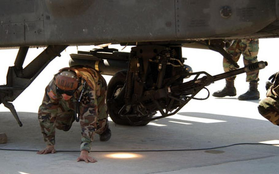 A 3-6 soldier from ducks under an Apache helicopter.